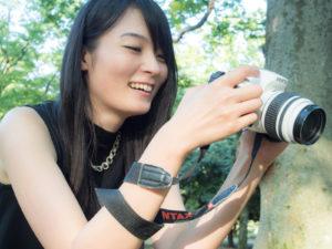 カメラを持って笑った女性の画像
