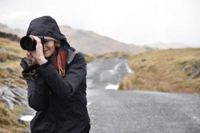 道路を撮影する女性カメラマンの画像