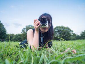 カメラを片手に写真を撮る女性の画像