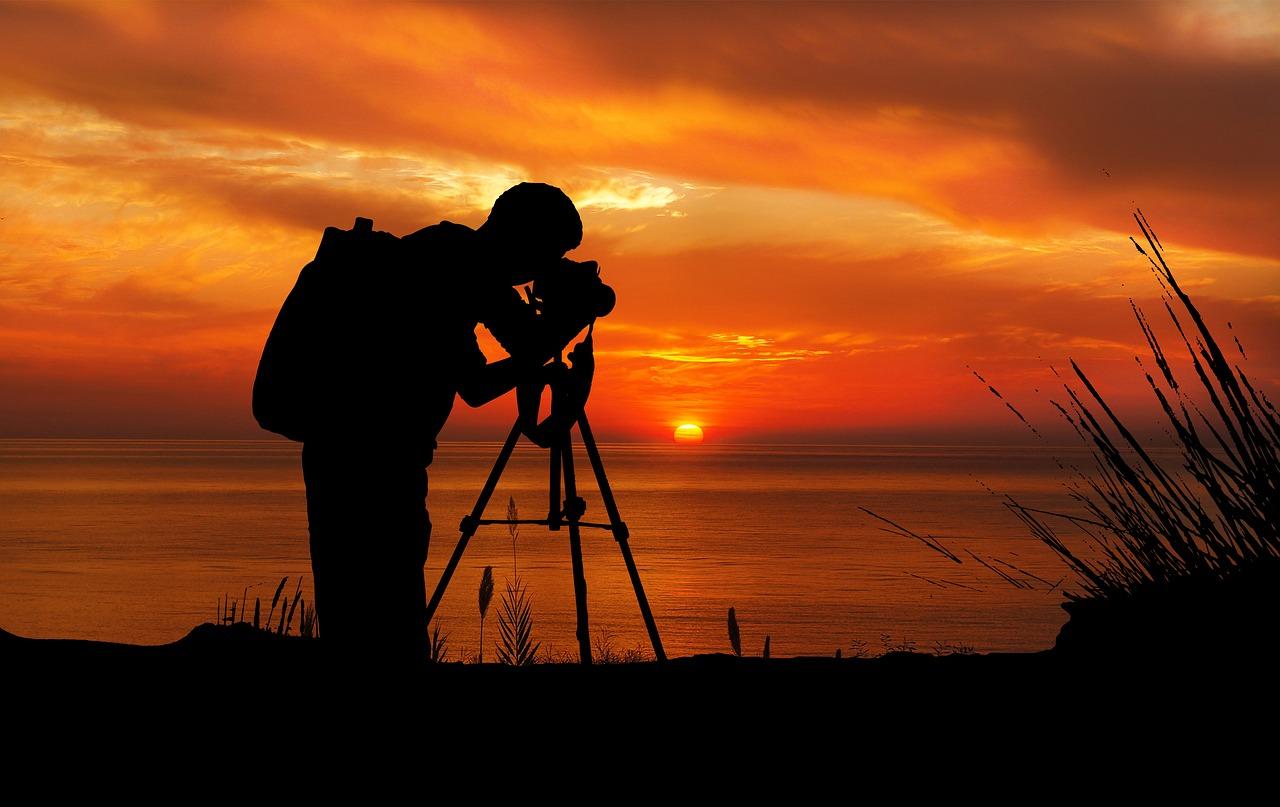 夕日を三脚を使って撮るカメラマンの画像