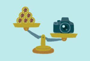 天秤にかけられたお金とカメラの画像